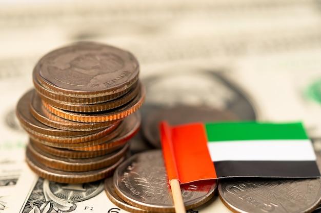 白い背景の上のアラブ首長国連邦の旗とコインのスタック。