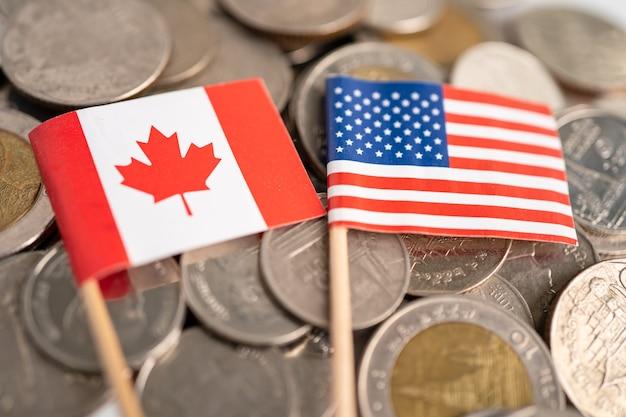 미국 미국과 캐나다 국기, 금융 개념이 있는 동전 더미.