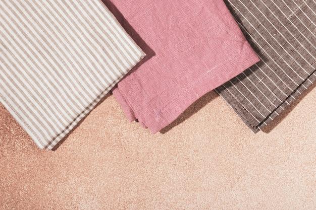 ベージュの漆喰の背景にナプキンを提供する色の布のスタック