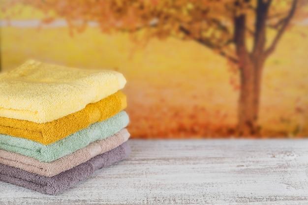 軽い木の板の上にカラフルなバスタオルのスタック。背景に秋の木。パステルカラーのコットンタオル。衛生、ファブリック、スパ、テキスタイルのコンセプト