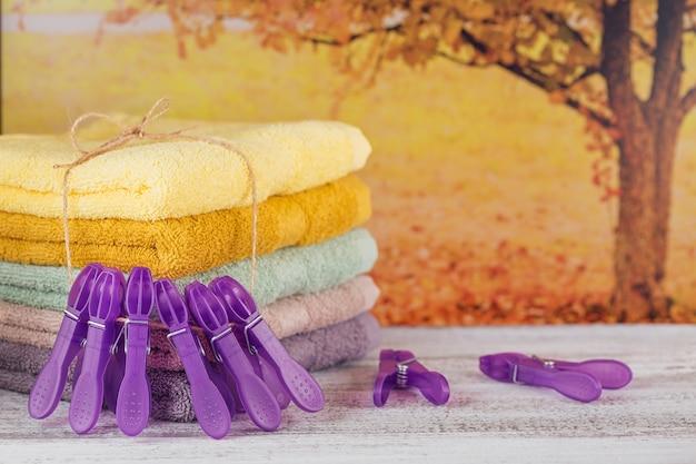明るい木の板に紫色の洗濯バサミとカラフルなバスタオルのスタック。背景に秋の木。パステルカラーのコットンタオル。衛生、ファブリック、スパ、テキスタイルのコンセプト