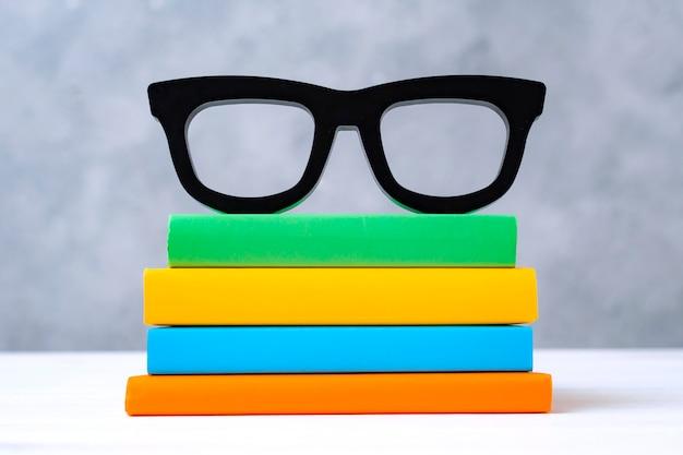 灰色の壁に白い木製のテーブルに眼鏡のカラフルな本のスタック。学校、読書、図書館、文学、研究、教育に戻るという概念。