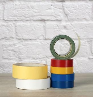 白いレンガの壁の背景にカラフルな絶縁テープのスタック
