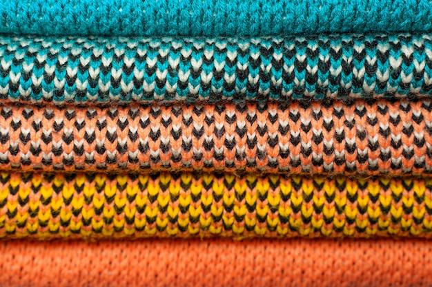 カラフルなニット生地、ニットの冬服のスタック。色とりどりのニット生地の背景