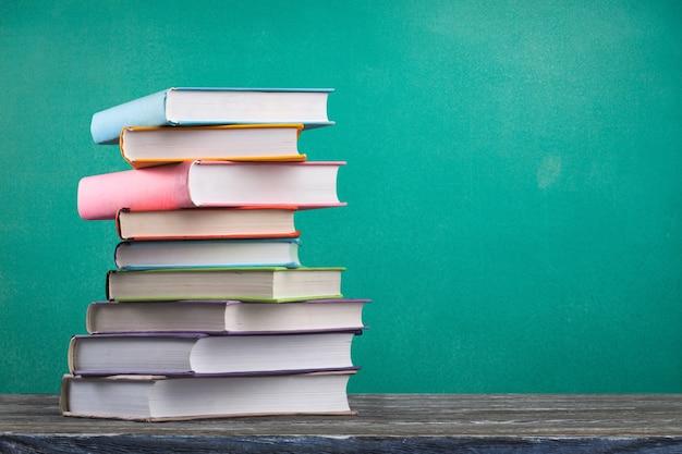 Стопка красочных школьных учебников на деревянном столе