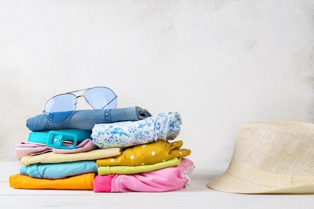 カラフルな夏服とアクセサリーのスタック。休暇の準備のコンセプトです。コピースペース。