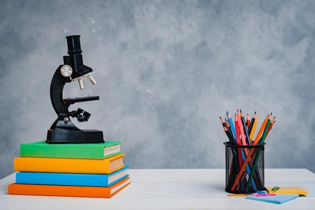 현미경 및 연필 다채로운 교과서의 스택