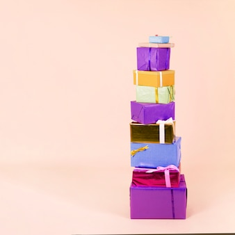 Stack of colorful wrapped gift boxes on beige background