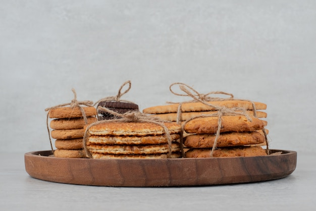 나무 접시에 밧줄으로 묶인 쿠키의 스택.