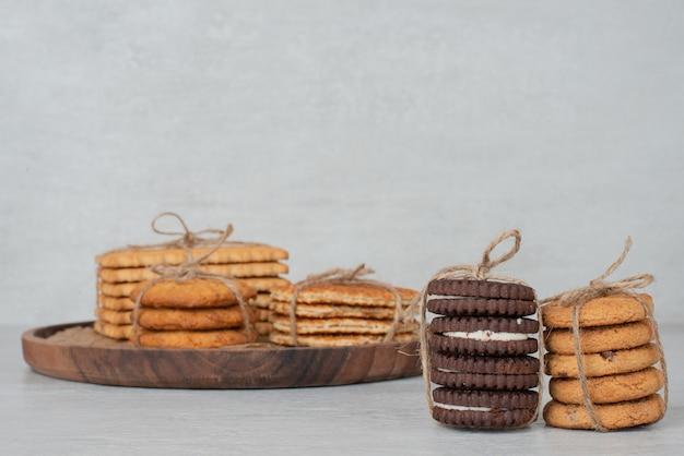 Стек печенья, перевязанный веревкой на деревянной тарелке.