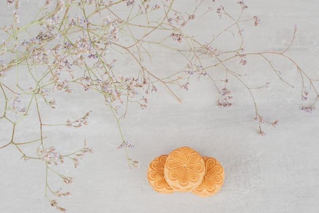 白い背景の上の植物の横にクリームとクッキーのスタック。