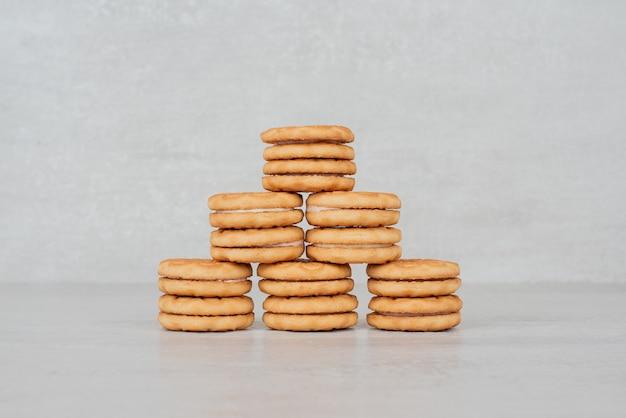 흰색 테이블에 크림과 함께 쿠키의 스택입니다.