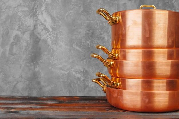 木製のテーブルの上の銅の調理鍋のスタックをクローズアップ