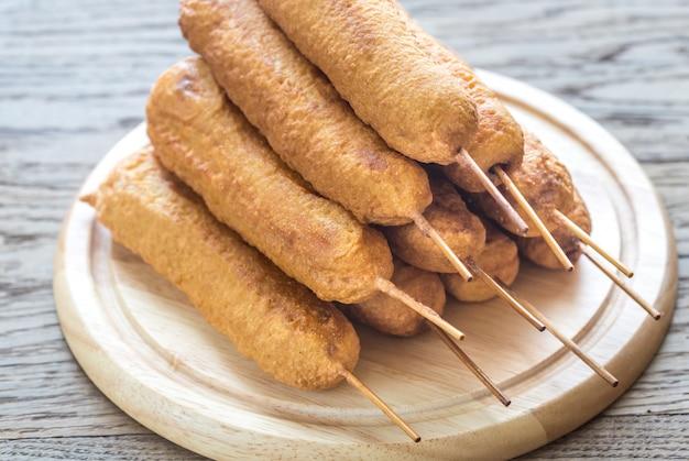 Стог кукурузных собак на деревянной доске