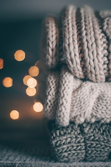 Стек уютных трикотажных свитера и гирлянды на деревянном фоне.