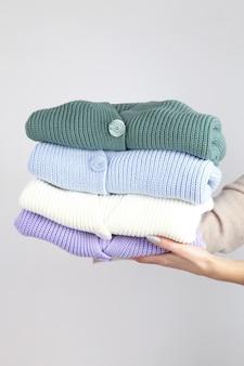 손에 아늑한 니트 스웨터의 스택
