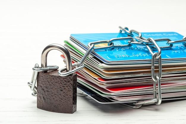 クレジットカードのスタックと白い背景で隔離されたチェーン付き南京錠クローズドアクセス