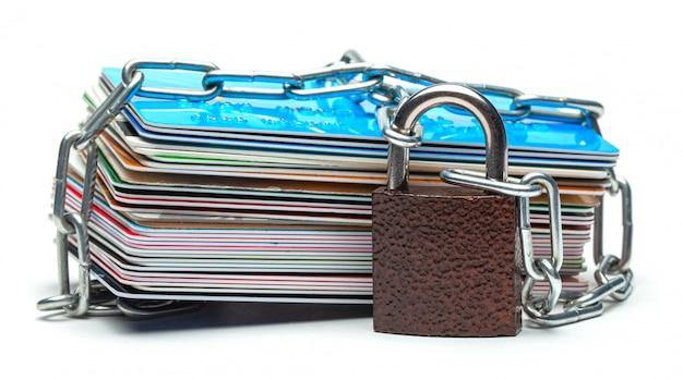 クレジットカードと白で隔離されるチェーン付き南京錠のスタック。クレジットカードへのクローズドアクセス、ブロック、ロック。