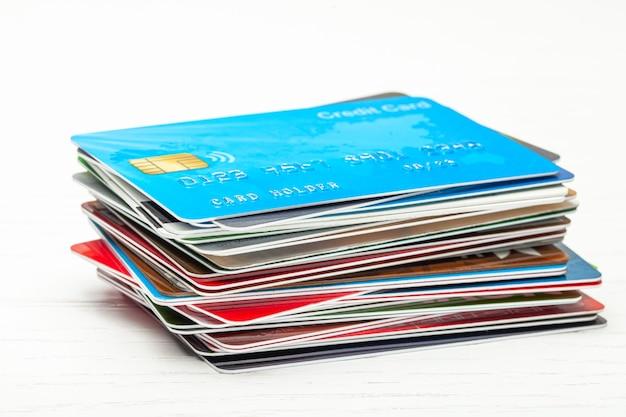 白い木製の背景に分離されたクレジットカードのスタック。