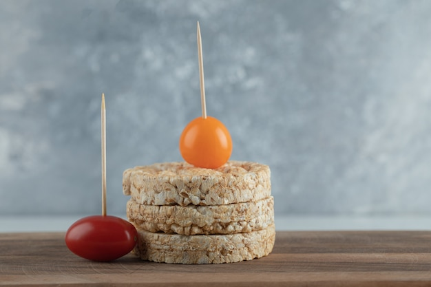 Стек хрустящих хлебцев и помидоров черри на деревянной доске