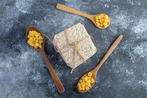 Стек хрустящих хлебцев и деревянные ложки сладких зерен на мраморе.