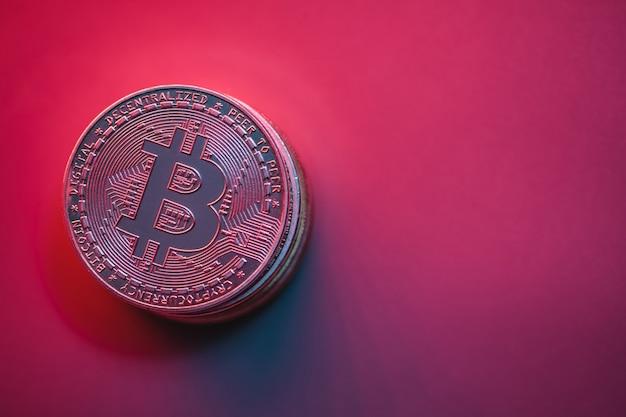 ネオン照明付きの赤、ピンクの背景に暗号コインのスタック。テキストの場所。