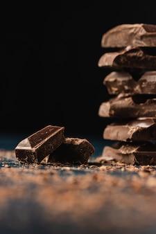 Стек кусочки темного шоколада на темной поверхности крупный план. копировать пространство