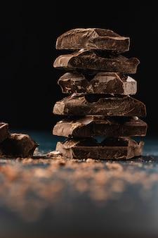 Стек из темного шоколада кусочки на темном.