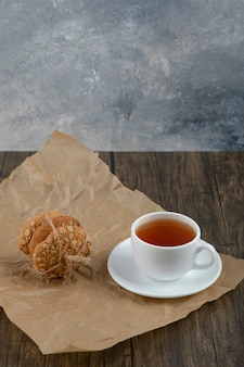 木製のテーブルの上においしいオートミールクッキーとお茶のスタック。