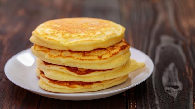 Стек вкусных блинов в белой тарелке на коричневой деревянной предпосылке. это домашний завтрак густой, мягкий, ароматный маслом.