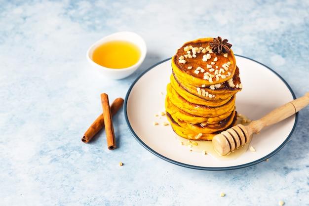 メープルシロップまたは蜂蜜とナッツを添えたおいしいカボチャのふわふわパンケーキのスタック。健康的な朝食。秋の食べ物。