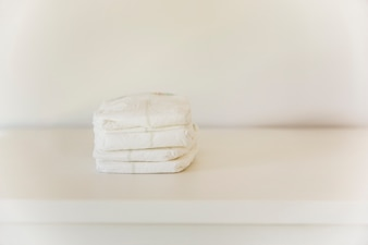 Stack of diaper on table against wall