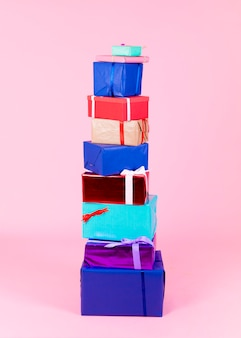 Stack of different colorful boxes against pink background
