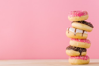 Stack of different donuts on pink