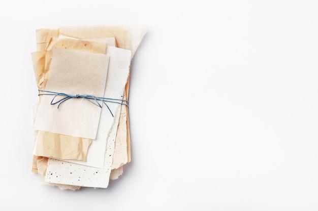 青い糸で結ばれた紙の異なる部分のスタック