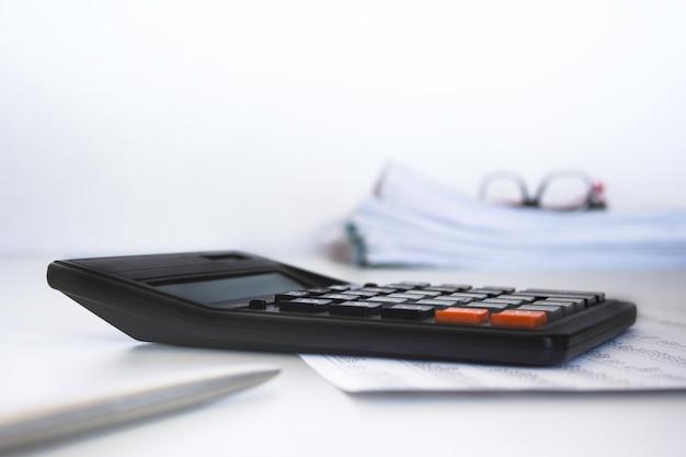 Стек документов, калькулятор, ручка на рабочем столе в бизнес-офисе. копировать пространство