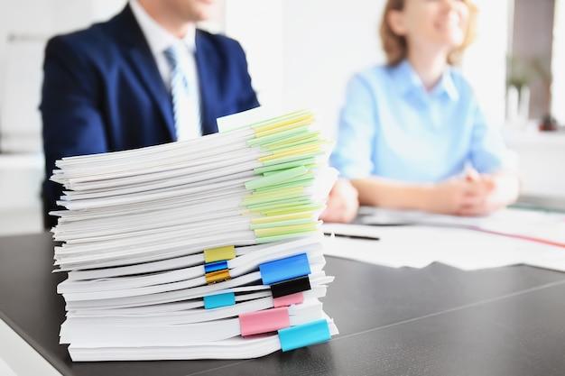 Стек документов на столе и размытые работники в офисе