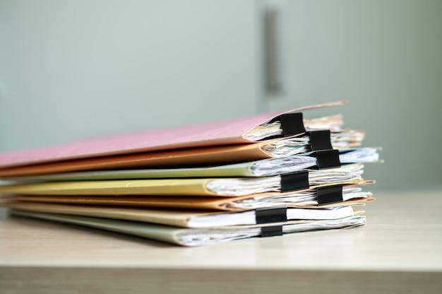 営業所のビジネスデスクに置かれたペーパークリップフォルダーを含むドキュメントのスタック。