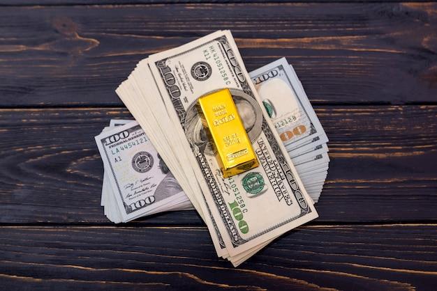 木製の背景にドルと金のインゴットのスタック