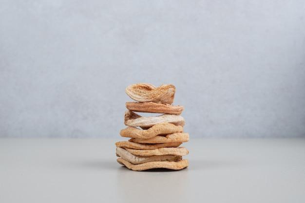흰색 표면에 말린 된 사과 칩의 스택