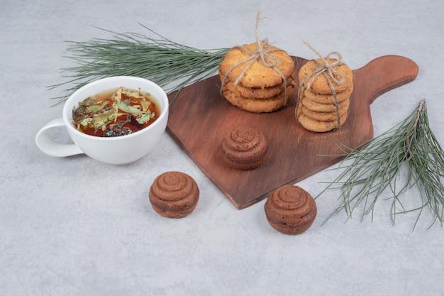 灰色のテーブルにお祝いのビスケットとお茶のスタック。高品質の写真
