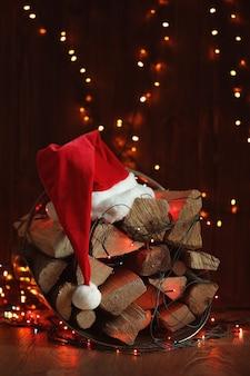 木製の表面に薪、花輪、サンタクロースの帽子のスタック