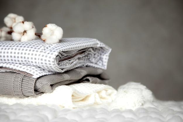 灰色の背景にさまざまなデザインパターンと綿の枝を持つ折り畳まれた暖かい毛布のスタック。ニット毛布。天然植物ベースの繊維の生産。製造。有機製品