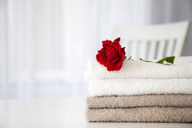 白いテーブルに赤いバラとグレーと白の色の新鮮なタオルのスタック。ランドリー、洗濯、ドライクリーニングの概念。コピースペース。