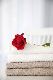흰색 테이블에 붉은 장미와 회색과 흰색 색상의 신선한 수건의 스택. 세탁, 세탁 또는 드라이 클리닝 개념.