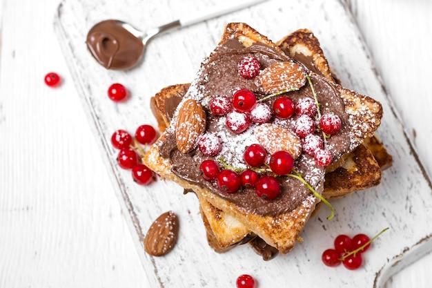 白い木製の背景にチョコレートクリーム、赤スグリ、アーモンドと揚げトーストのスタック