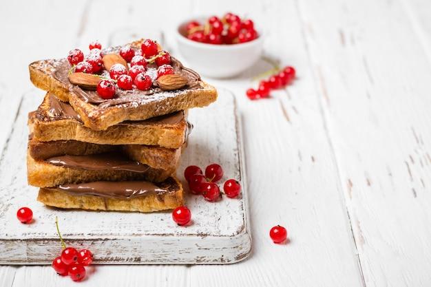 흰색 나무 배경에 초콜릿 크림, 붉은 건포도, 아몬드를 넣은 튀긴 토스트 스택 프리미엄 사진