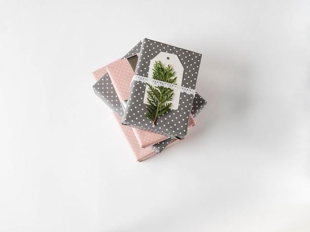 Стопка подарков в розово-серой бумаге в горошек