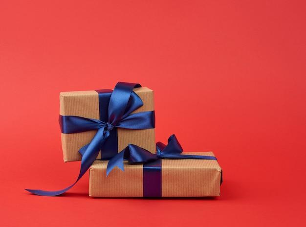 茶色のクラフトペーパーとシルクブルーのリボンに包まれた贈り物のスタック