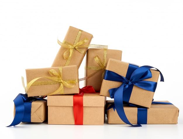 茶色のクラフトペーパーに包まれ、分離されたボックスシルクブルーとレッドのリボンで結ばれた贈り物のスタック